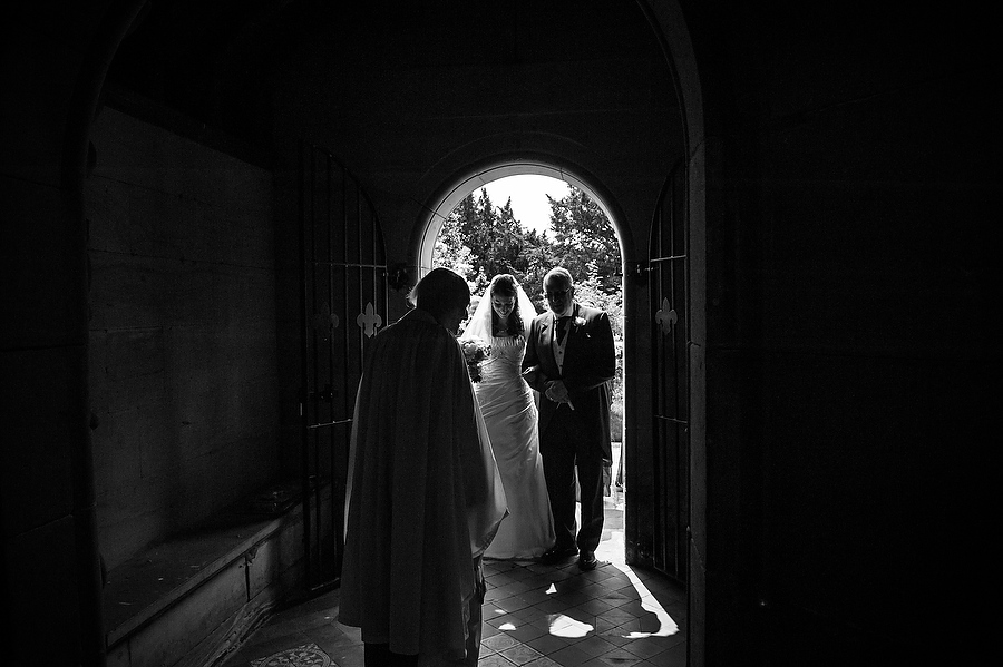 Candid moment as the bride arrives through church doorway at St Johns Church in Armitage by Contemporary Wedding Photographer Barry James