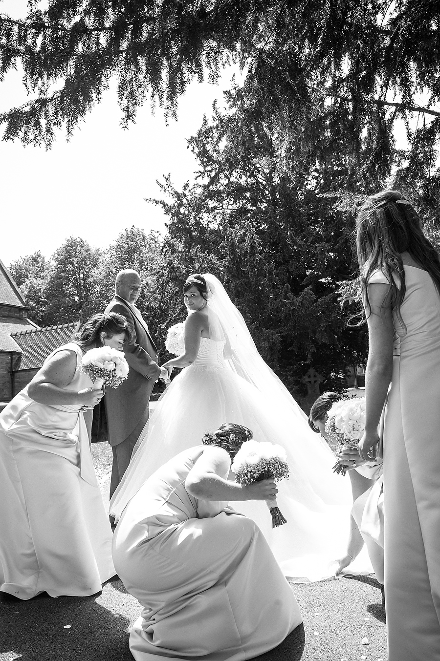A beautiful moment between bride and bridesmaids candidly captured at St Marks Church in Great Wyrley by Cannock Wedding Photographer Barry James