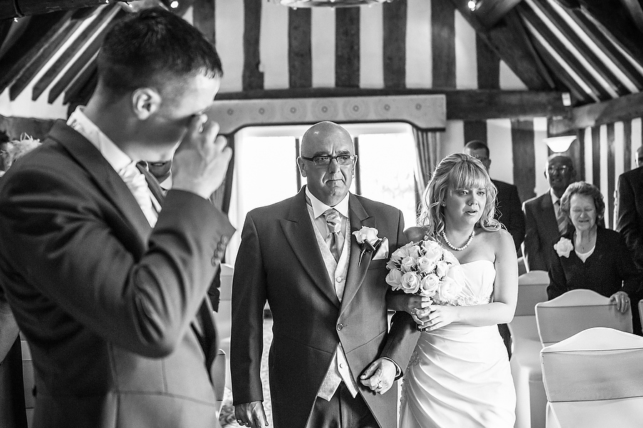 Candid photo showing grooms emotional reaction to seeing his bride arrive at Colin Lewis Suite in Moat House by Stafford Wedding Photographer Barry James
