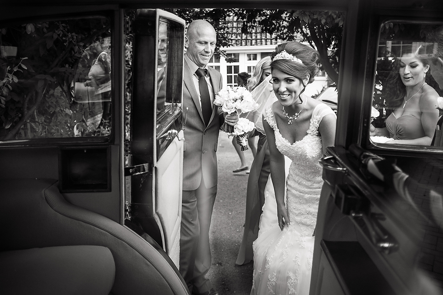 Storytelling moment as bride excitedly arrives at her wedding car before wedding at Alrewas Hayes in Burton by Burton Reportage Wedding Photographer Barry James